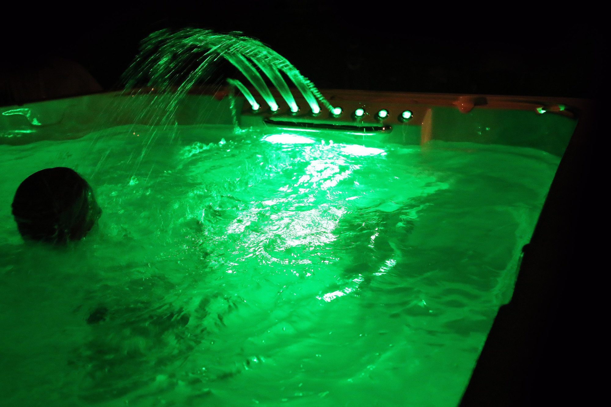 Swimmer in a swim spa with added Northern Lights and Waterfall Jets