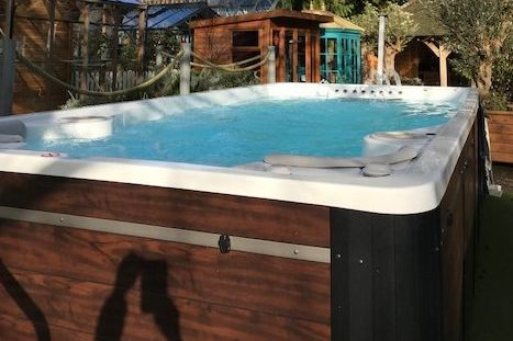 Hydropool Swim Spa on display outdoors next to garden buildings